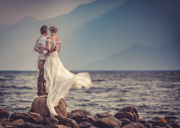 Couple in wedding clothes standing in front of a lake