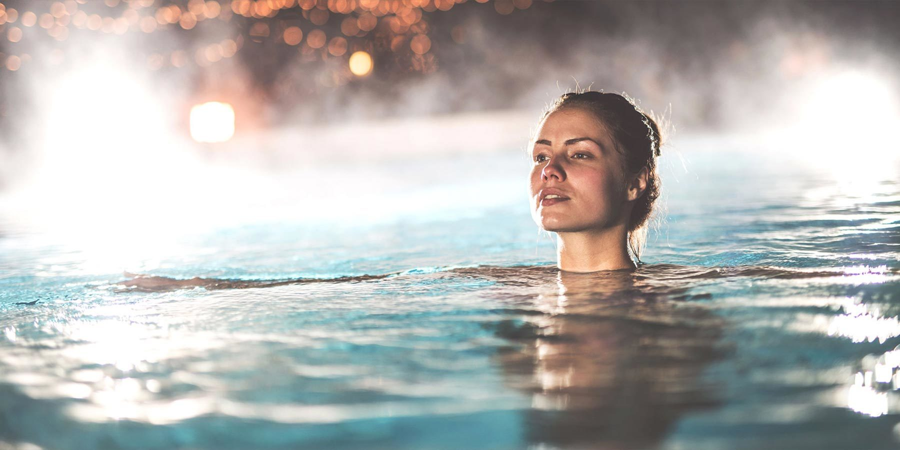 Young woman in hot pool at night