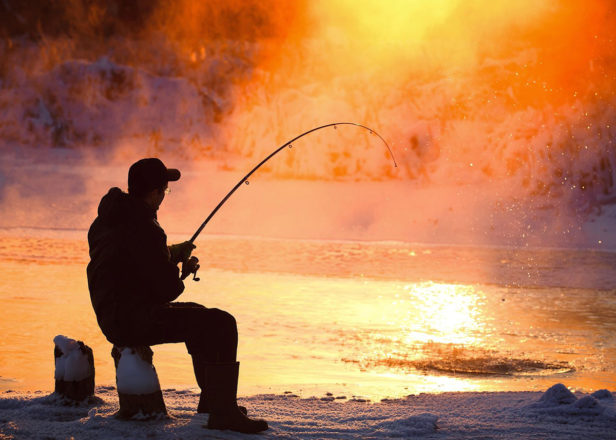 Man ice fishing at sunset