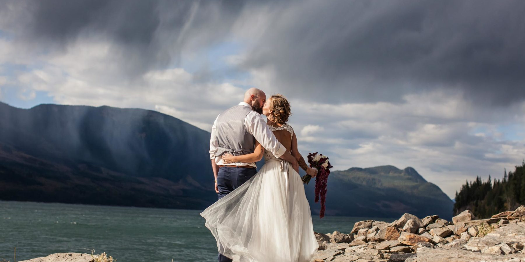 Newlyweds kissing in front of Arrow Lake